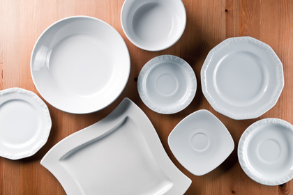 Very elegant china and everyday ceramics tableware (plates, dessert plates, bowl, saucer) on wooden table, directly above.